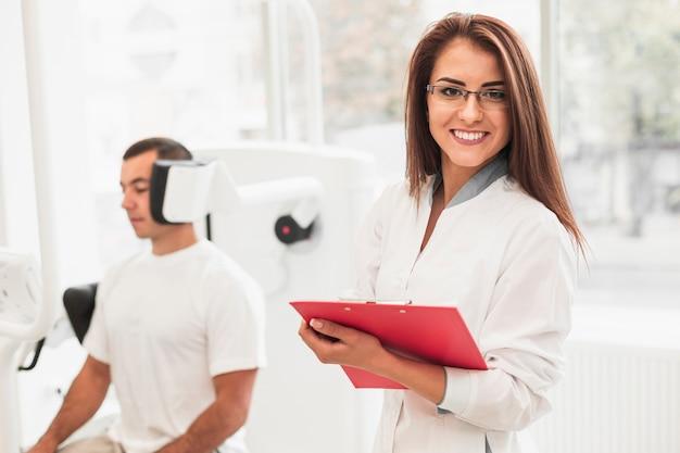Ärztin, die klemmbrett hält und fotografen betrachtet