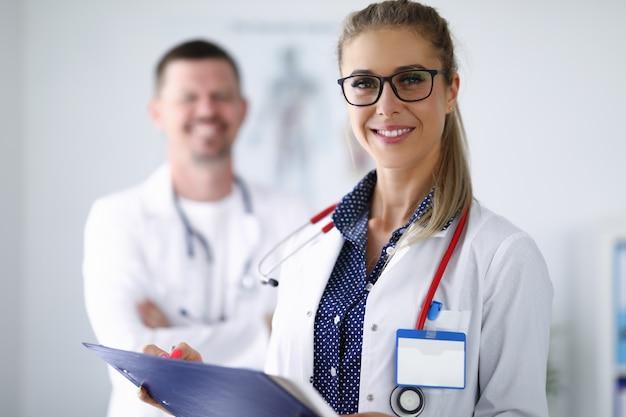 Ärztin, die lächelt und zwischenablage hinter ihrem kollegen hält, steht. medina dienstleistungen aller richtungen konzept