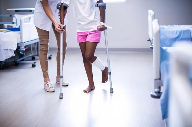 Ärztin, die mädchen hilft, mit krücken in der abteilung zu gehen