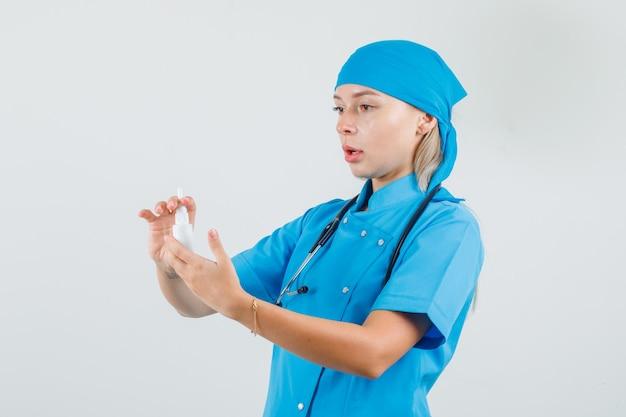 Ärztin, die medizinische flasche in blauer uniform hält und vorsichtig schaut