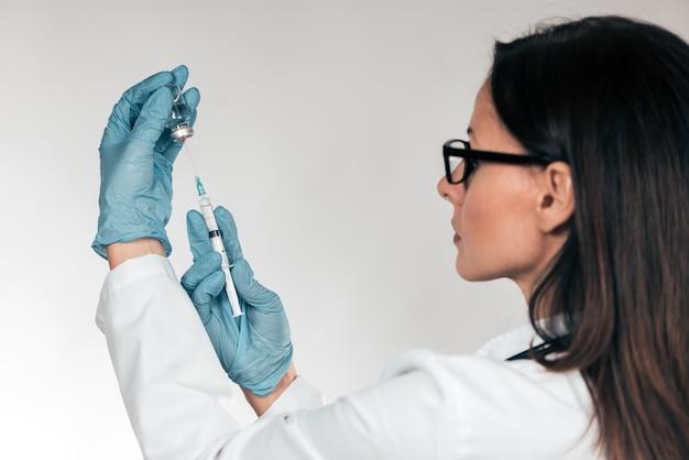 Ärztin, die medizinische spritze mit nadel in der ampulle fertig wird zur geduldigen einspritzung hält.