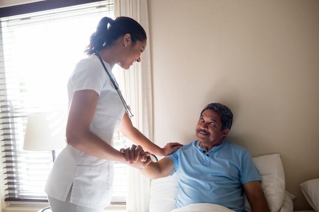 Ärztin, die mit älterer patientin im schlafzimmer interagiert