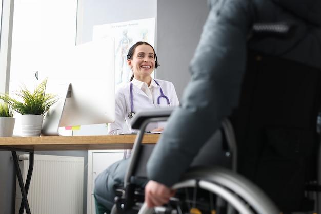 Ärztin, die mit behinderten patienten im rollstuhl in der klinik kommuniziert. medizinische assistenz