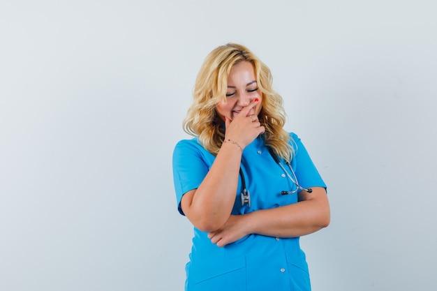 Ärztin, die mit der hand auf mund in der blauen uniform lacht und fröhlichen raum für text sucht