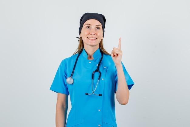 Ärztin, die mit fingerzeichen in uniform aufblickt und fröhlich schaut. vorderansicht.