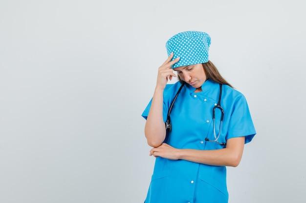 Ärztin, die mit hand auf kopf in blauer uniform steht und müde aussieht. vorderansicht.