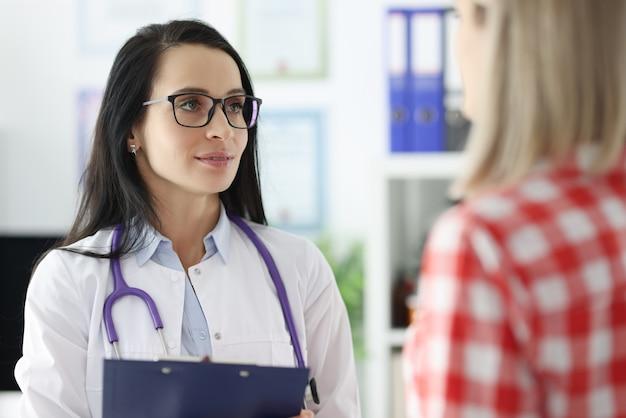 Ärztin, die mit patientin in der klinik kommuniziert. beratung des konzepts führender fachärzte