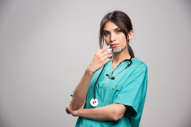 Ärztin, die mit spritze auf grau aufwirft