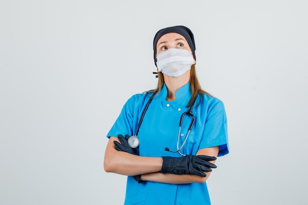Ärztin, die mit verschränkten armen in uniform, maske, handschuhen aufblickt