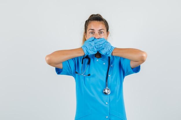 Ärztin, die mund mit händen in blauer uniform bedeckt