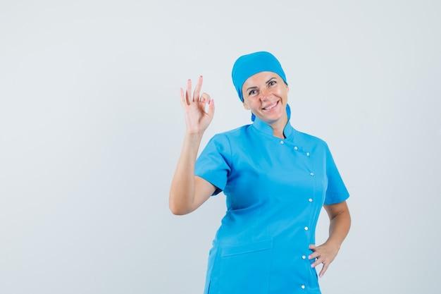 Ärztin, die ok geste in der blauen uniform tut und zuversichtlich schaut, vorderansicht.