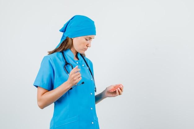 Ärztin, die packung der pillen in der blauen uniform hält und verärgert schaut