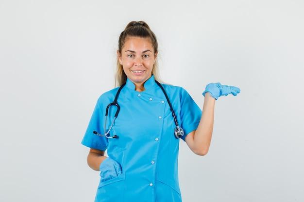 Ärztin, die palme als fang etwas in der blauen uniform erhebt