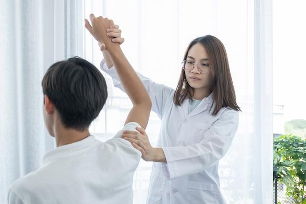 Ärztin, die physiotherapie durchführt, indem sie die schulter eines männlichen patienten verlängert.