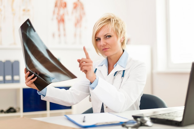 Ärztin, die röntgenbild prüft