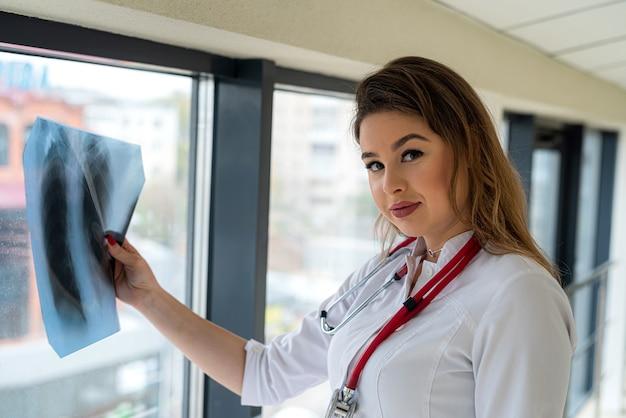 Ärztin, die röntgenfilm der brust untersucht und fragen zur patientendiagnose im krankenhaus hat.