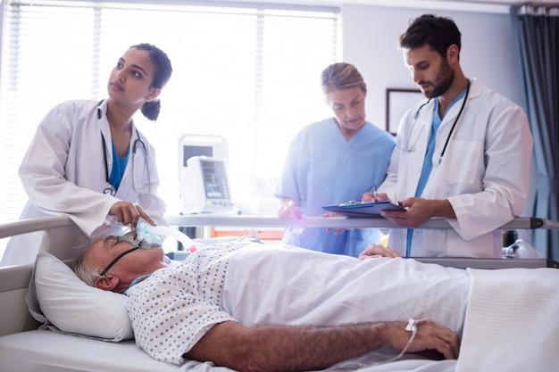 Ärztin, die sauerstoffmaske auf patientengesicht setzt