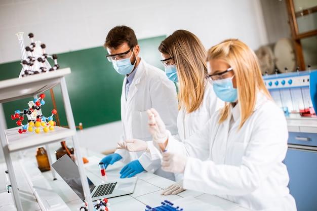 Ärztin, die schützende gesichtsmaske und sicherheitsbrille im labor hält, hält nadelspritze und medizinfläschchen-impfstoffflasche