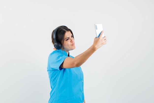 Ärztin, die selfie macht, während sie musik in blauer uniform genießt