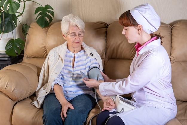 Ärztin, die sich zu hause mit älterem patienten auf einem ledersofa berät