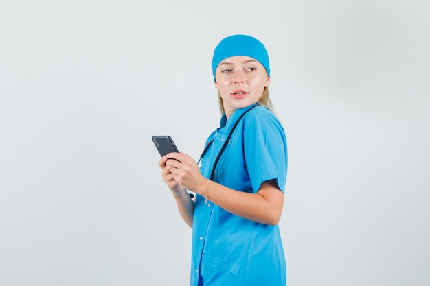 Ärztin, die smartphone hält und in blauer uniform beiseite schaut und niedlich schaut