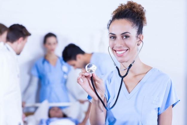 Ärztin, die stethoskop in richtung zur kamera und zu anderem doktor überprüft einen patienten hinten im krankenhaus zeigt