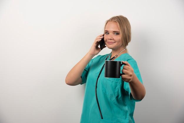 Ärztin, die tee beim gespräch mit telefon hält.