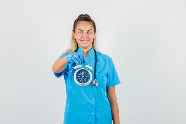 Ärztin, die wecker in blauer uniform hält