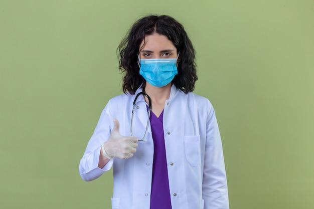 Ärztin, die weißen kittel mit stethoskop in der medizinischen schutzmaske mit lächeln auf gesicht trägt, zeigt daumen oben stehend auf lokalisiertem grün
