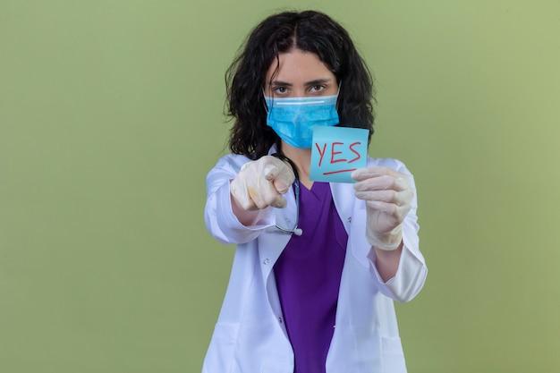 Ärztin, die weißen kittel mit stethoskop in der medizinischen schutzmaske trägt, die erinnerungspapier mit ja-wort zeigt, das auf kamera mit finger zeigt, der ernsthaft auf isoliertem grün schaut