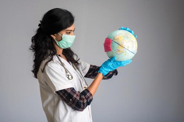 Ärztin, die weltkugel mit einer medizingesichtsmaske hält. welt-epidemie des coronavirus-konzepts.