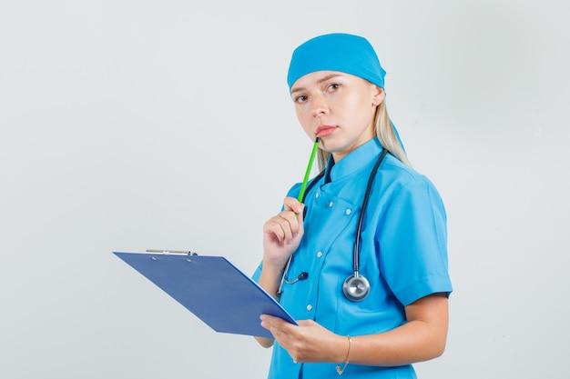 Ärztin, die zwischenablage mit bleistift nahe mund in der blauen uniform hält und beschäftigt schaut