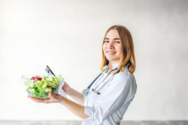 Ärztin ernährungsberaterin, die gesundes essen in den händen hält.