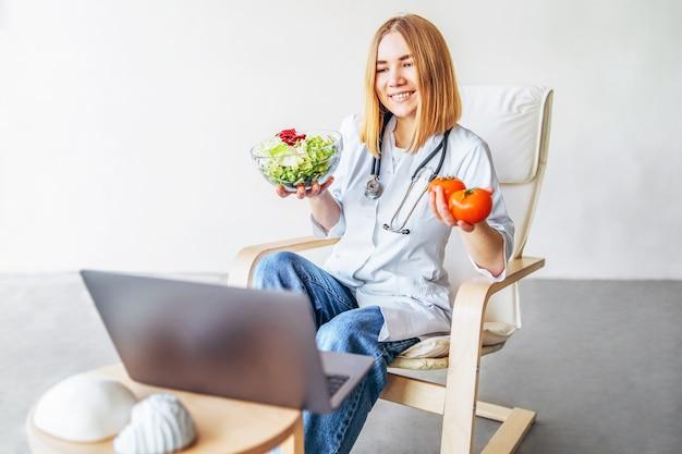 Ärztin ernährungsberaterin führt online-beratung mit laptop durch.