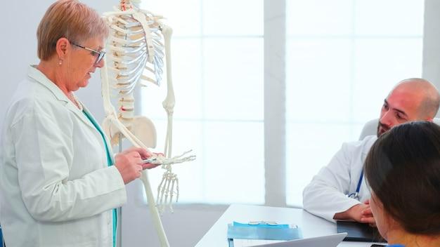 Ärztin für radiologie, die präsentation mit skelett vor medizinischem personal hält. klinik-expertentherapeut, der mit kollegen über krankheiten spricht, mediziner, der im sitzungssaal arbeitet