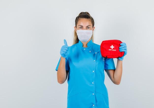 Ärztin hält erste-hilfe-kasten mit daumen nach oben in blauer uniform