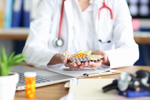 Ärztin hält verschiedene medikamente in den händen