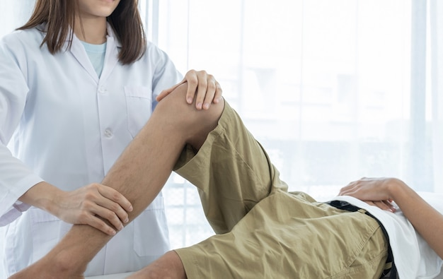 Ärztin hände tun physiotherapie durch die verlängerung des beins und knies eines männlichen patienten.