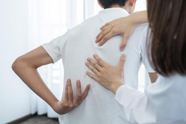 Ärztin hände tun physiotherapie durch die verlängerung des rückens eines männlichen patienten.
