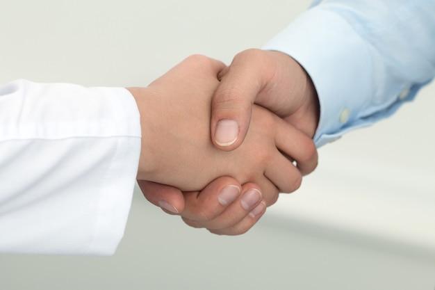 Ärztin händeschütteln mit männlichem patienten. konzept für partnerschaft, vertrauen und medizinische ethik. handschlag mit zufriedenem kunden. gesundheitswesen und medizinisches konzept