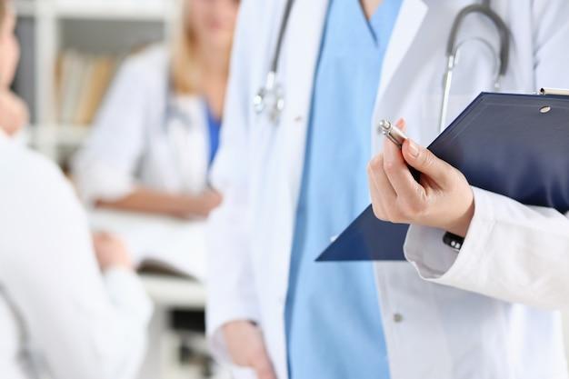 Ärztin halten zwischenablage pad und füllen krankengeschichte liste