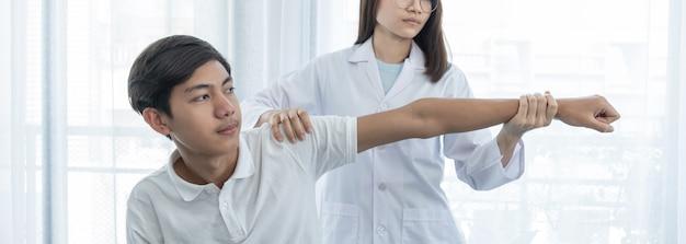 Ärztin hand, die physiotherapie tut, indem sie die hand eines männlichen patienten ausstreckt.