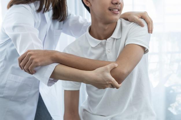 Ärztin hand, die physiotherapie tut, indem sie die schulter eines männlichen patienten verlängert.