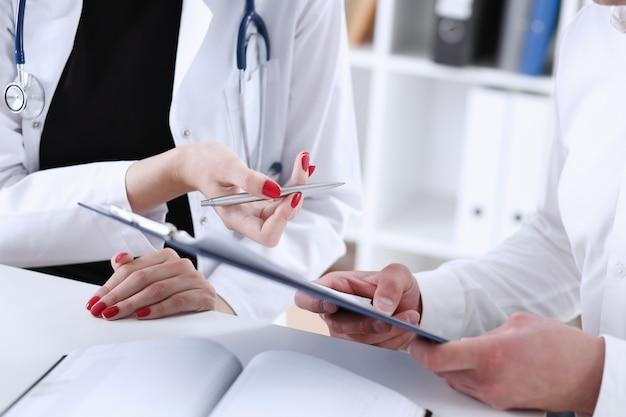 Ärztin hand halten silbernen stift und zeigt pad