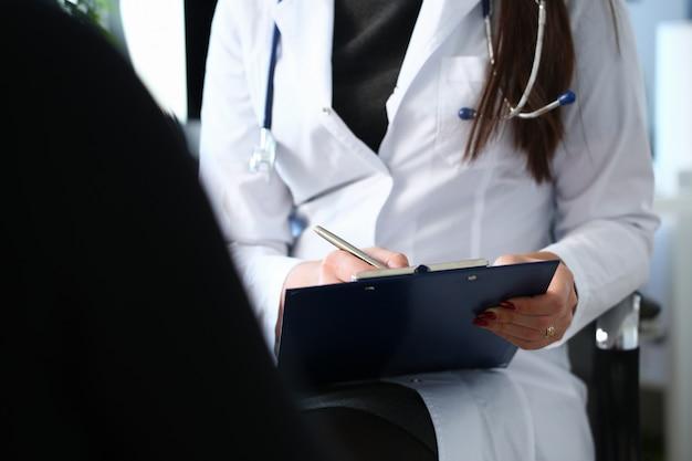Ärztin hand halten silberstift füllung patientengeschichte liste am klemmbrett pad.