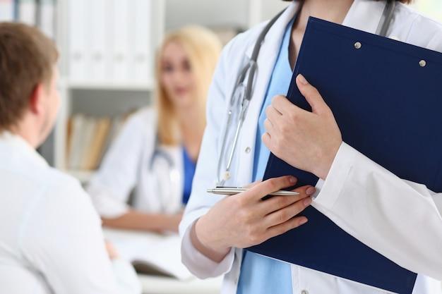 Ärztin hand halten silberstift füllung patientenliste