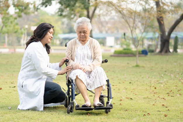 Ärztin hilft und pflegt asiatische senioren oder ältere frauen, die im rollstuhl auf der krankenstation sitzen, gesundes, starkes medizinisches konzept