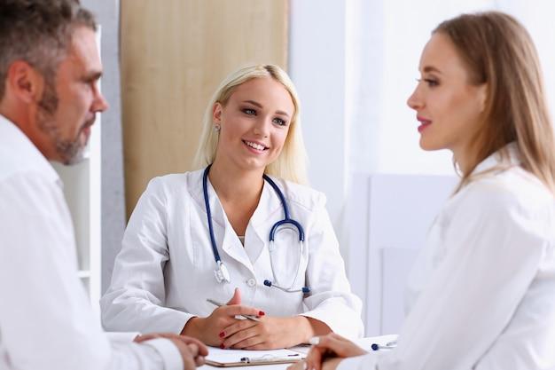 Ärztin hören aufmerksam junges paar
