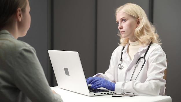 Ärztin im gespräch mit patientin während des besuchs in der arztpraxis.