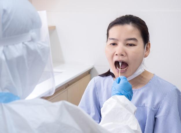 Ärztin im persönlichen schutzanzug mit wattestäbchen zur entnahme einer bukkalen tupferprobe für coronavirus-tests bei patienten mit einem risiko für eine coronavirus-infektion. covid-19 und impfkonzept